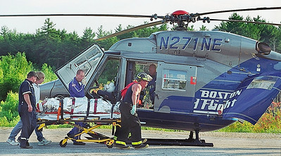 7/7/04 m.moorephoto           news---The victim of a plane crash at Silver Ranch Airpark in Jaffrey is wheeled to a Boston Med Flight helicopter.