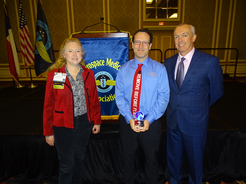 Bauer Lecturer Morgan Sandercock (center) receives a token of appreciation from AsMA President Valerie Martindale and Vernon MacDonald representing the sponsor of the educational activity, KBRwyle.