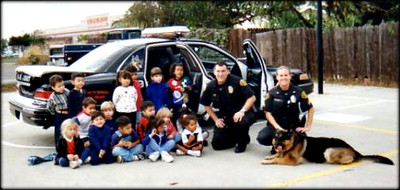 "Public relations was a very important part of my job with Ruger.  Here we are in Garden Grove, CA with a group of special needs children on Halloween.  We staged a mock robbery for the kids where we had a ""bad guy"" steal a bucket full of Halloween candy that we had brought for them.  The ""bad guy"" came out of no where (totally surprised the kids) and ran off with the bucket.  I sent Ruger on a search and he found the ""bad guy"" and the candy was returned to the kids...needless to say, Ruger was a hero!  Photo by Jayson Carter"
