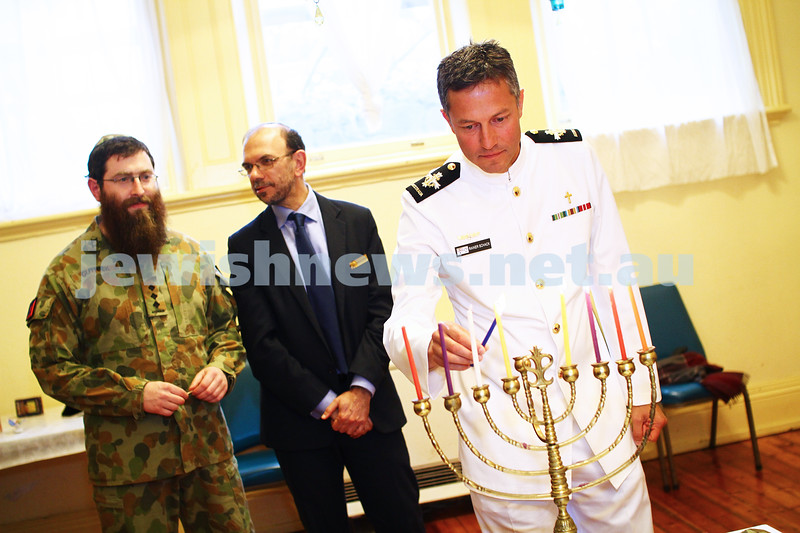 5-012-13. Last day of Chanukah. East Melbourne Hebrew Congregation. Rabbi David Gutnick, Jewish Chaplain with the Australian Defense Force, organised a candle lighting ceremony incorporating members of the ADF and guests that included Felix and Yvonne Sher, parents of Private Greg Sher who was killed in Afganistran. Pictured her is Naval chaplain Rainer Schack lighting a candle. Photo: Peter Haskin