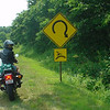 """""""Connie O'Connor riding her 1983 Honda Nighthawk 650 in the Blue Ridge Mountains ponders a curious road sign."""" - Tim O'Connor."""