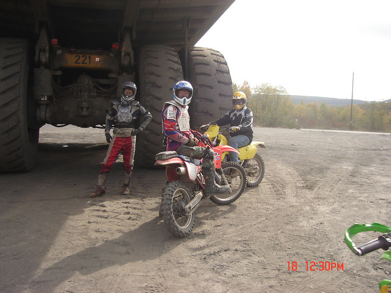 """""""This was taken by some strip mines in upstate Pennsylvania. I am on the old 1985 CR250 with my friend, Mark, each 50-year-old kids. My 14-year-old son is standing and my 16-year-old son took the shot. I always loved riding but now that my kids are into it we ride regularly and we all have a blast. When I had my first son my wife pushed me to grow up and get rid of that old dirt bike, little did I know that I would be working hard to keep up with each son on the very same bike (now rebuilt a few times). - Russ Bailey"""