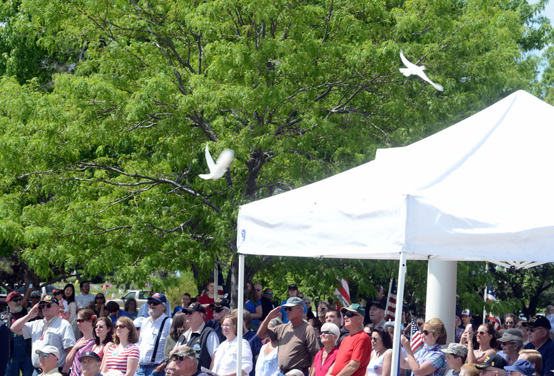 White doves fly over the crowd during the playing of taps during the Memorial Day ceremony Monday, May 30, 2016, at Resthaven Memory Gardens north of Loveland. (Photo by Craig Young / Loveland Reporter-Herald)