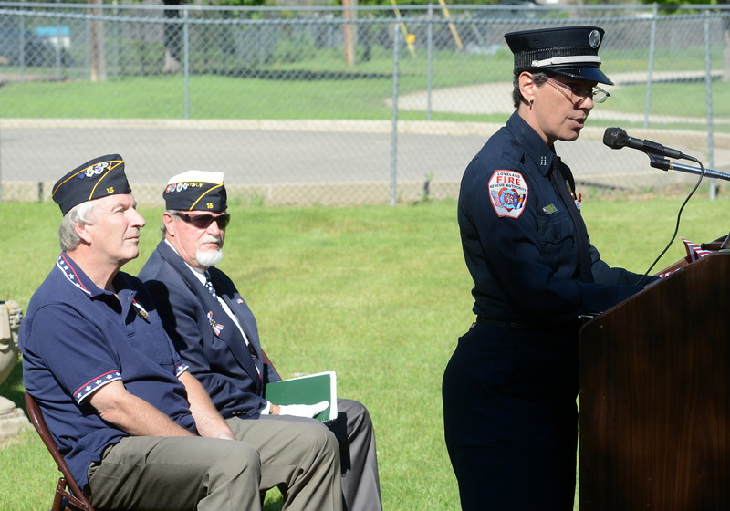 Loveland Fire Rescue Authority Capt. Pat Mialy speaks to the crowd during the Associated Veterans of Loveland's Memorial Day ceremony Monday, May 30, 2016, at Loveland Burial Park. Seated behind her are John Sommerrock, senior vice commander of Loveland's American Legion Post 15, left, and Associated Veterans Club chaplain Charlie Nash. (Photo by Craig Young / Loveland Reporter-Herald)