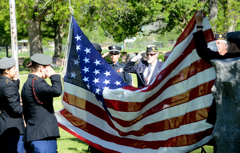 Members of the Thompson School District's Junior ROTC color guard prepare to raise the American flag at the beginning of the Memorial Day service at Loveland Burial Park on Monday, May 30, 2016. Saluting the flag are Loveland Fire Rescue Authority Capt. Pat Mialy, left, and Associated Veterans chaplain Charlie Nash. (Photo by Craig Young / Loveland Reporter-Herald)