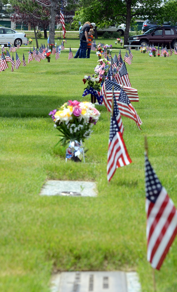 """Loveland resident Fred Glass, his mother-in-law, Janet Meyer of Fort Collins, and other family members place decorations on the graves of veterans Monday, May 30, 2016, at Resthaven Memory Gardens north of Loveland. Meyer said for the past eight or 10 years, the family has been picking out undecorated gravestones -- """"folks who don't have anyone else to care for them."""" (Photo by Craig Young / Loveland Reporter-Herald)"""