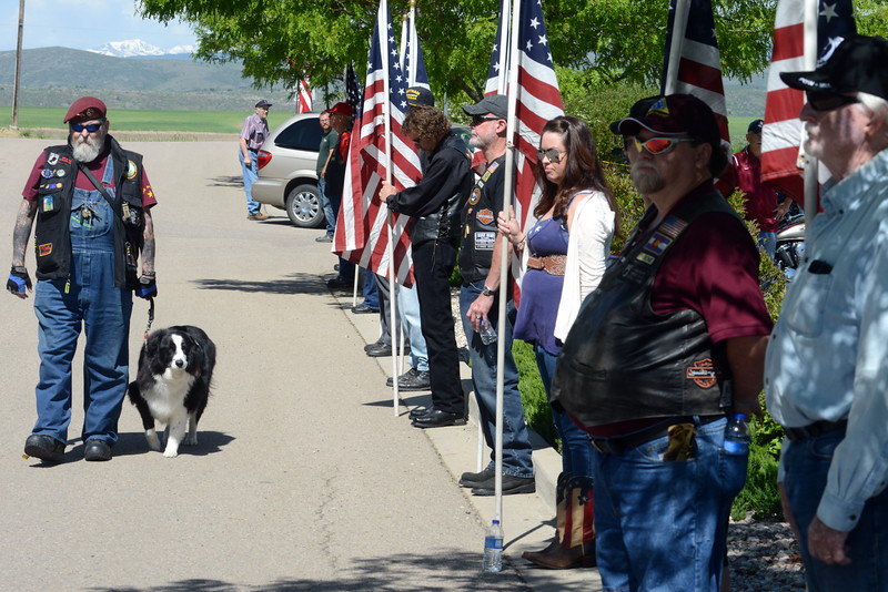 Loveland resident Lucky Davis, an Air Force veteran, walks with his service dog past fellow members of the Patriot Guard during the Memorial Day event at Resthaven Memory Gardens north of Loveland on Monday, May 30, 2016. (Photo by Craig Young / Loveland Reporter-Herald)