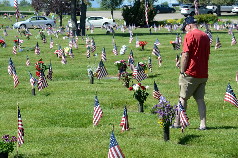 """Bill Bertram, a Vietnam War veteran, pauses at the grave of a veteran in Resthaven Memory Gardens north of Loveland on Monday, May 30, 2016. Bertram said he doesn't know anyone buried there. """"I'm just saying hey,"""" he said."""