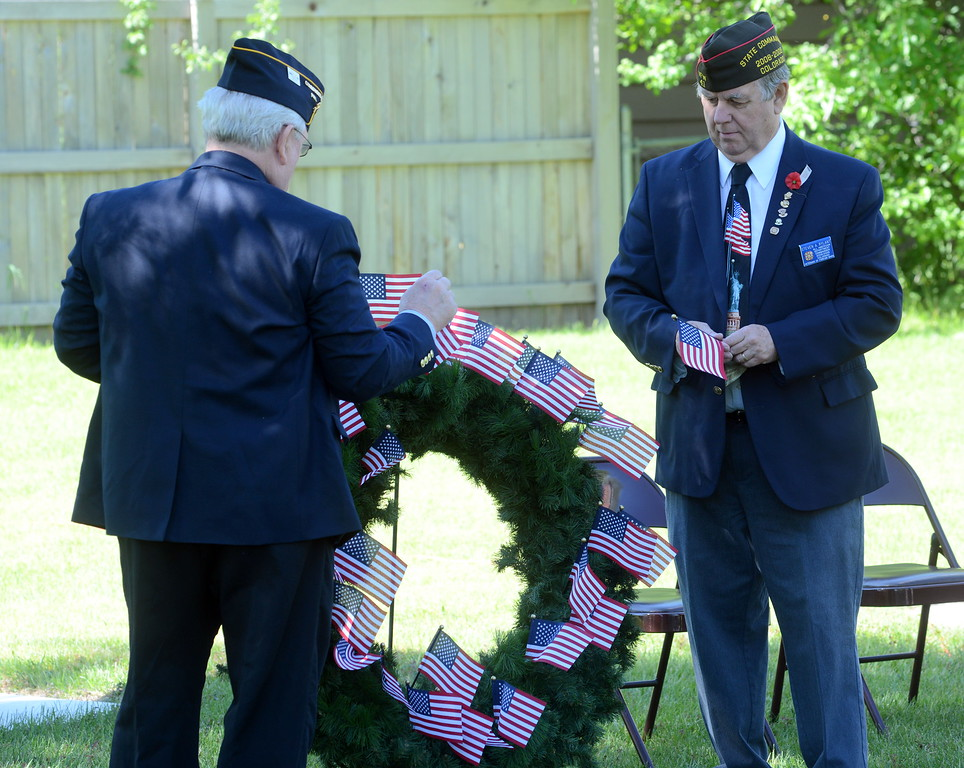 Steven Rylant, quartermaster of the Veterans of Foreign Wars Post 41, right, and Bart Bartholomew, commander of American Legion Post 15, place flags on a wreath as the names are read of the 25 members of the two organizations who have died in the past year. The ceremony took place during the Associated Veterans of Loveland's Memorial Day event Monday, May 30, 2016. (Photo by Craig Young / Loveland Reporter-Herald)