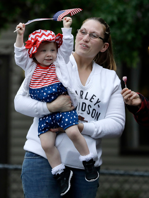 . Amanda Ackerman holds 1-year-old Ryleigh Ackerman as they watch a Memorial Day parade, Monday, May 29, 2017, in Bridgewater, N.J. (AP Photo/Julio Cortez)