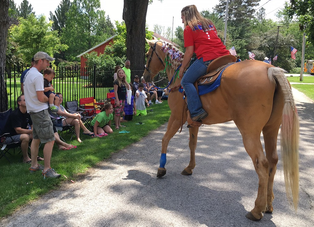 . Richard Payerchin - The Morning Journal <br> Haze Showalter, 19 months, is held by his father, Greg Showalter, of Amherst, as they meet Puddles the horse and his owner, Kara Rennert of Berlin Heights, in the Florence Township/Birmingham Memorial Day Parade on May 29, 2017. Hundreds of people across northern Ohio came out to honor Amerca\'s fallen defenders in community Memorial Day services.