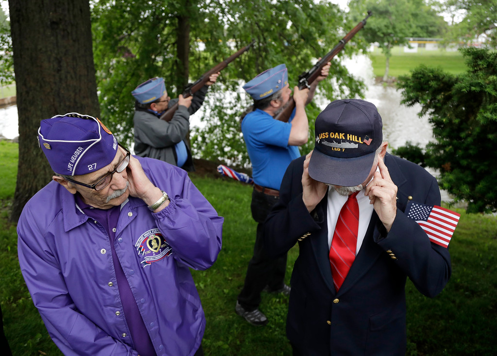 . Herb Colie, left, who served with the 4th Battalion 60th artillery, and Jim Benning, rght, who served as a second class machinist\'s mate on the USS Oak Hill during the Vietnam War, cover their ears as John Marsigliano, back left, and Chris Moeller, both of the Sons of the American Legion, do a gun salute during a Memorial Day observance, Monday, May 29, 2017, in Bridgewater, N.J. (AP Photo/Julio Cortez)