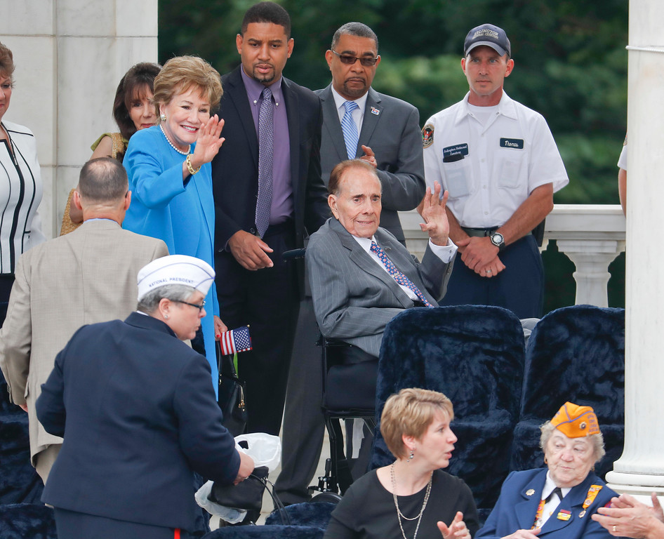 . Former Senate Majority Leader Bob Dole, right, and his wife former Sen. Elizabeth Dole, left, acknowledge applause from crowd as they arrive to take their seats at the Memorial Amphitheater in Arlington National Cemetery in Arlington, Va., Monday, May 29, 2017, before the start of a Memorial Day ceremony. (AP Photo/Pablo Martinez Monsivais)