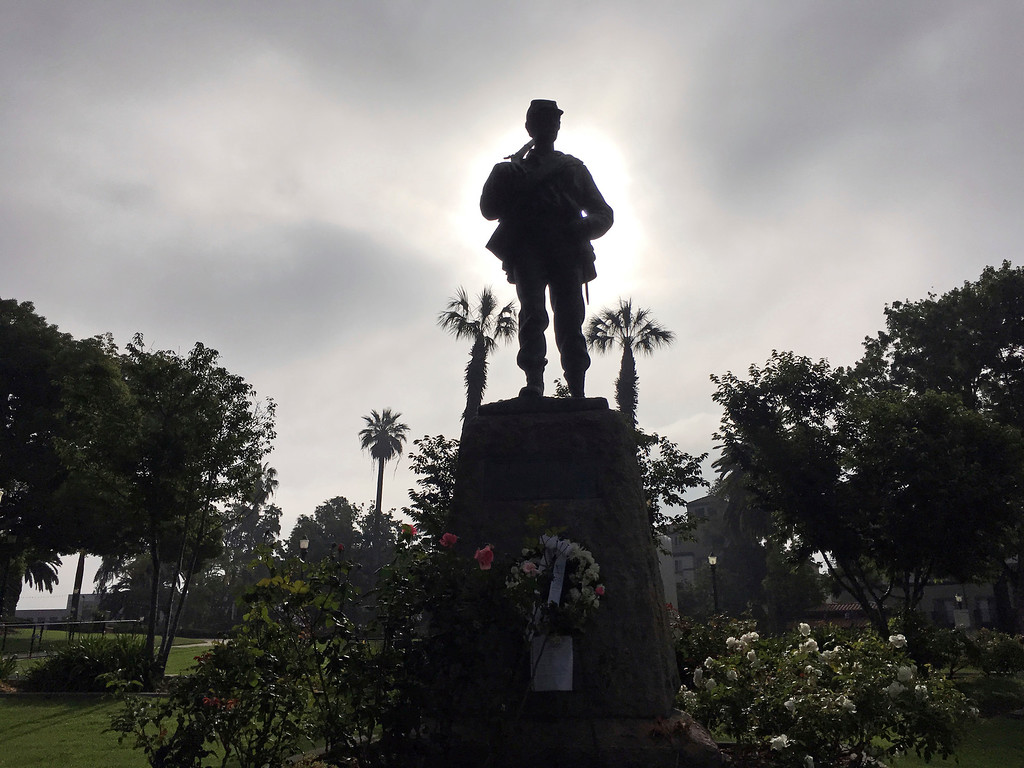 """. A Civil War statue dedicated to \""""the defenders of the Union\"""" is silhouetted by the Memorial Day sunrise in Pasadena, Calif., on Monday, May 29, 2017. (AP Photo/John Antczak)"""