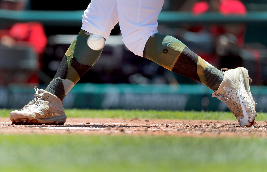 . St. Louis Cardinals\' Matt Carpenter wears camouflage socks as part of his Memorial Day uniform as he fouls a ball off his leg while batting during the first inning of a baseball game against the Los Angeles Dodgers Monday, May 29, 2017, in St. Louis. (AP Photo/Jeff Roberson)
