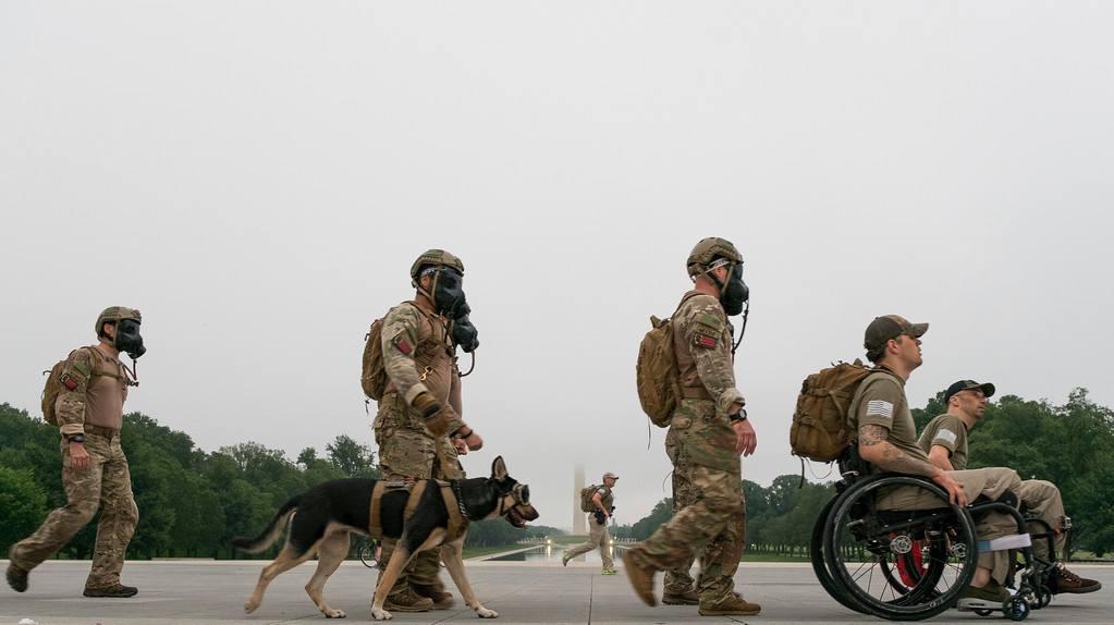 """. Members of the veterans support group \""""Ruck to Remember\"""" walk along the National Mall in Washington, Monday, May 29, 2017, as they continue their Memorial Day march to Arlington National Cemetery. (AP Photo/J. David Ake)"""