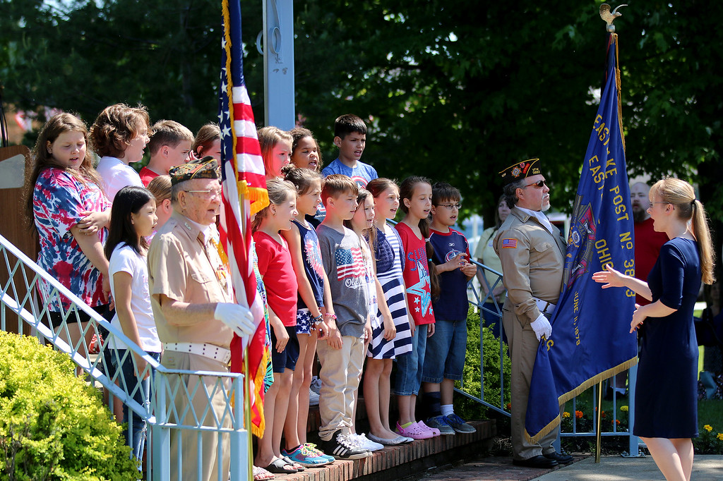 . Jonathan Tressler - The News-Herald Students from the Willoughby-Eastlake Schools\' Jefferson Elementary School sing the God Bless America, flanked by VFW Post 678 honor guardsmen 92-year-old Mickey Pugel, left, and U.S. Navy veteran John Lloyd May 29 behind Eastlake City Hall.