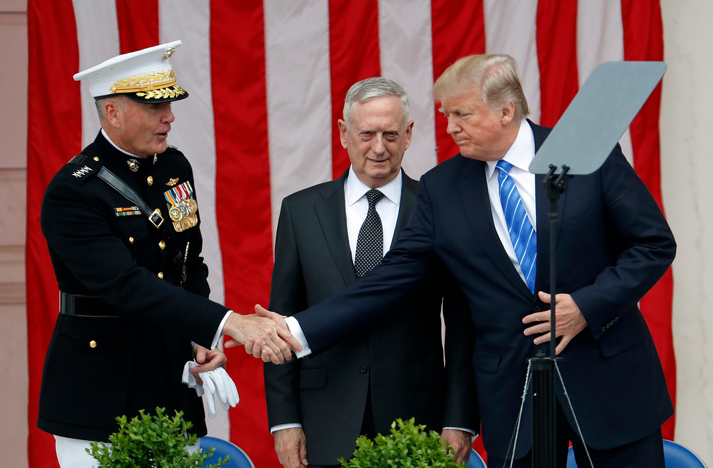 . President Donald Trump, right, shakes hands with Joint Chiefs Chairman Gen. Joseph Dunford, left, as Defense Secretary Jim Mattis, center, watches at the Memorial Amphitheater in Arlington National Cemetery in Arlington, Va., Monday, May 29, 2017, during a Memorial Day ceremony. (AP Photo/Pablo Martinez Monsivais)