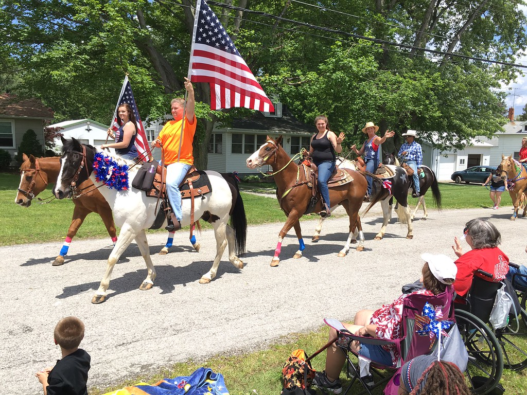 . Richard Payerchin - The Morning Journal <br> Riders from Clearview Stables of Berlin Heights carry flags as they and their horses march participate in the Florence Township/Birmingham Memorial Day Parade on May 29, 2017. The riders were among dozens of participants in the parade around Birmingham, the village near the crossroads of SR 60 and SR 113 in Florence Township, Erie County.