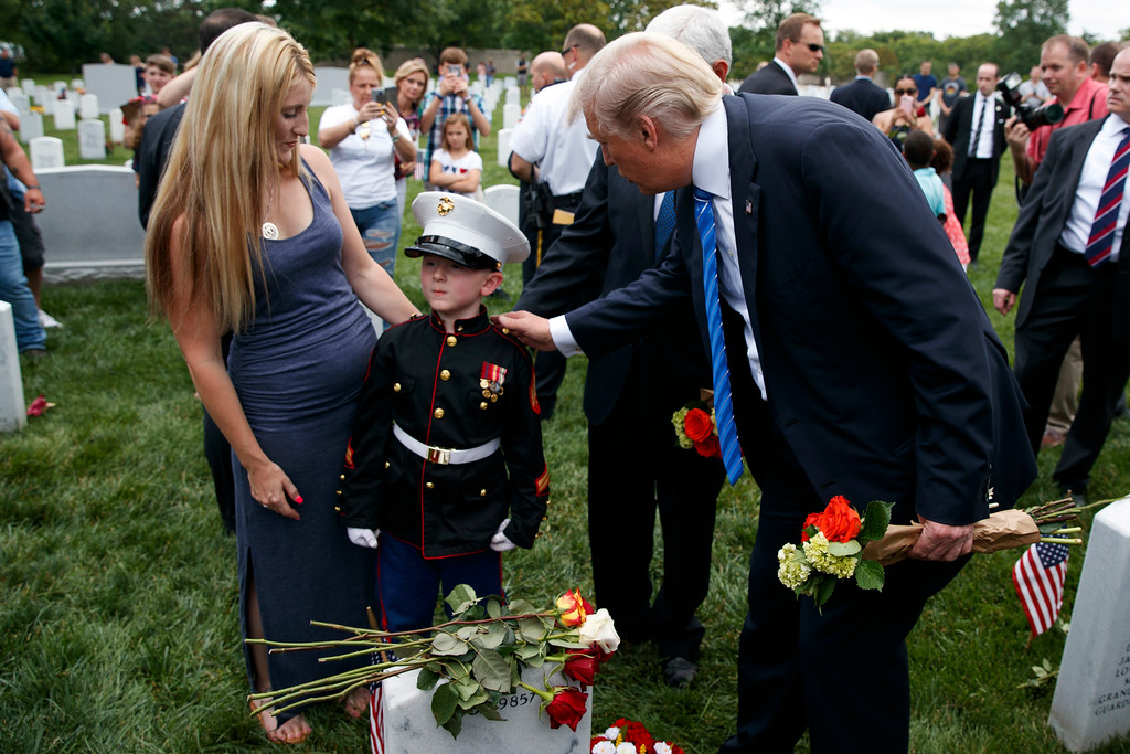 . Brittany Jacobs, left, watches as her 6-year-old son Christian Jacobs talks with President Donald Trump in Section 60 of Arlington National Cemetery, Monday, May 29, 2017, in Arlington, Va. Jacobs father, Marine Sgt. Christopher Jacobs, was killed in 2011. (AP Photo/Evan Vucci)