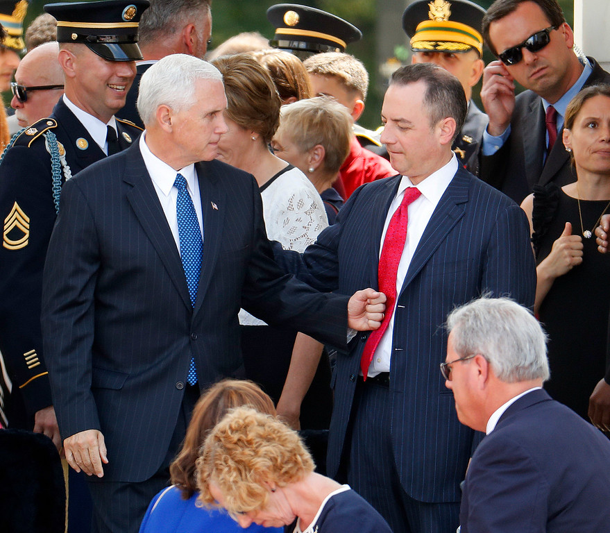 . Vice President Mike Pence, left, taps Chief of Staff Reince Priebus, in his stomach as they arrive at the Memorial Amphitheater in Arlington National Cemetery in Arlington, Va., Monday, May 29, 2017, during a Memorial Day ceremony. (AP Photo/Pablo Martinez Monsivais)