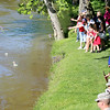 Jonathan Tressler - The News-Herald<br /> Participants in the Perry community's Memorial Day observance May 29 toss flowers into the Grand River near Mason's Landing Park to honor U.S. service veterans who lost their lives at sea.
