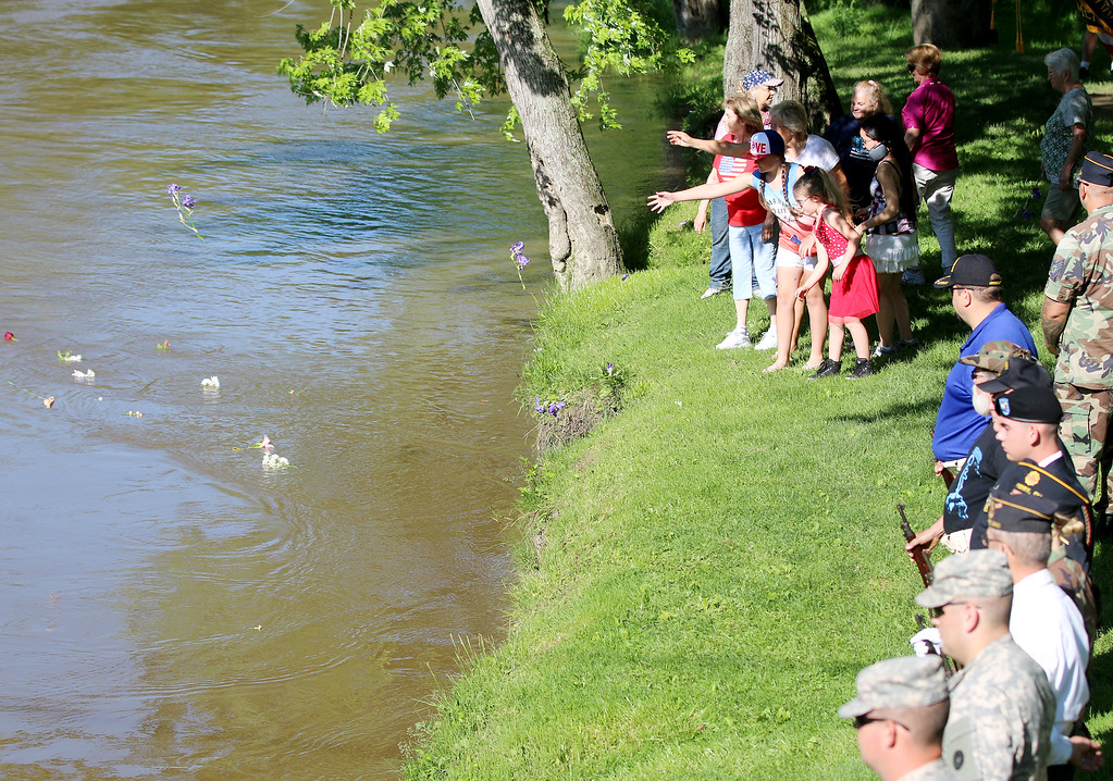 . Jonathan Tressler - The News-Herald Participants in the Perry community\'s Memorial Day observance May 29 toss flowers into the Grand River near Mason\'s Landing Park to honor U.S. service veterans who lost their lives at sea.
