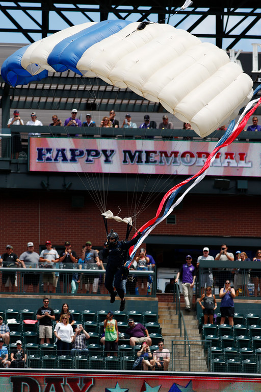 """. A member of the U.S. Air Force\'s \""""Wings of Blue\"""" parachute team drops into Coors Field as part of Memorial Day celebration before the Colorado Rockies host the Seattle Mariners in an interleague baseball game Monday, May 29, 2017, in Denver. (AP Photo/David Zalubowski)"""