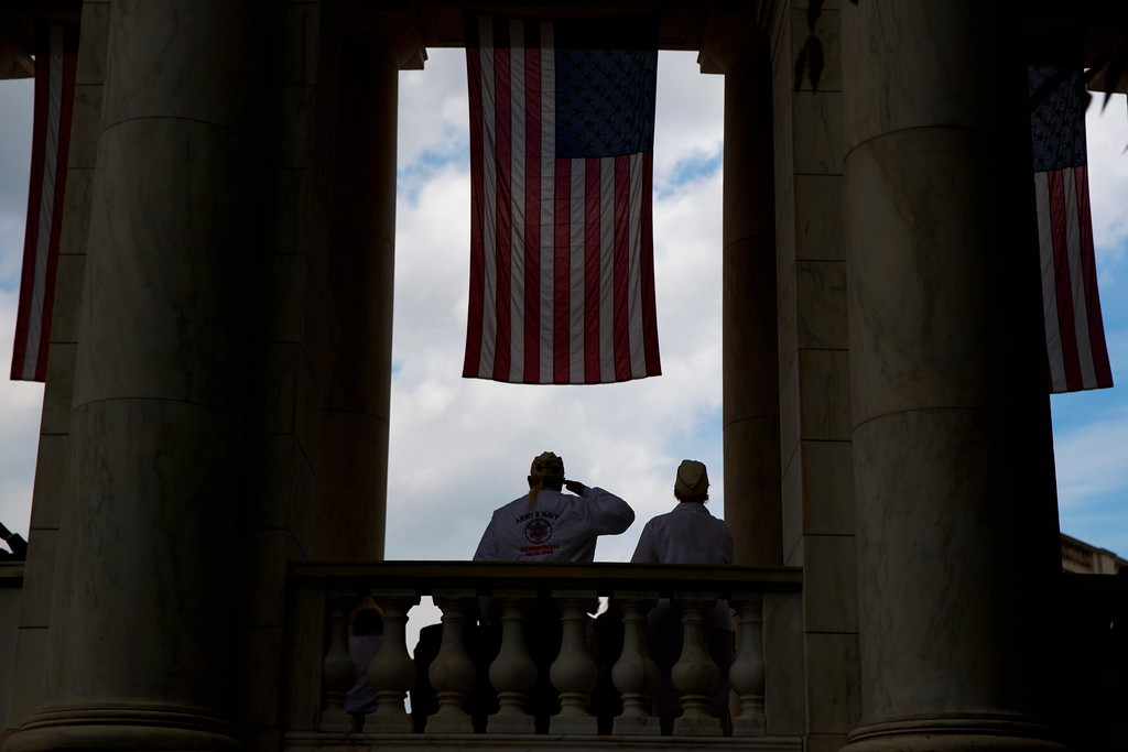 """. A man salutes as \""""Taps\"""" is played during a Memorial Day ceremony attended by President Donald Trump at Arlington National Cemetery, Monday, May 29, 2017, in Arlington, Va. (AP Photo/Evan Vucci)"""