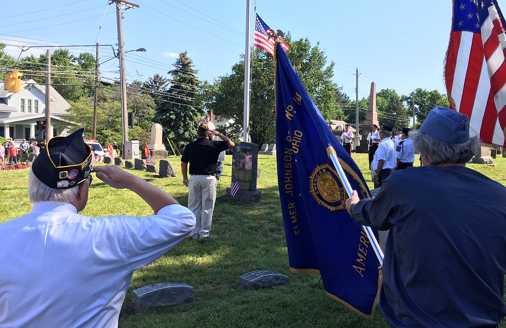 . Richard Payerchin - The Morning Journal <br> John Pena, commander of the Amherst VFW Post 1662, center, leads the community salute at the Amherst Veterans Memorial in the Cleveland Street Cemetery before the Amherst Memorial Day Parade on May 29, 2017. Hundreds of people came out to communities across Lorain County for Memorial Day services.