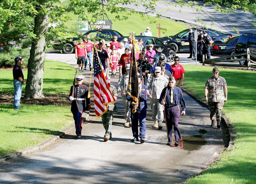 . Jonathan Tressler - The News-Herald The Perry Memorial Day procession makes its way toward the Grand River at Mason\'s Landing Park on Vrooman Road May 29, where flowers were tossed into the river to honor soldiers whose lives have been lost at sea in their service to our country.