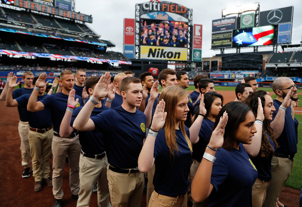 . Enlistees in the Navy take the United States Armed Forces Oath of Enlistment during a Memorial Day ceremony on the field before a baseball game between the New York Mets and the Milwaukee Brewers, Monday, May 29, 2017, in New York. (AP Photo/Julie Jacobson)