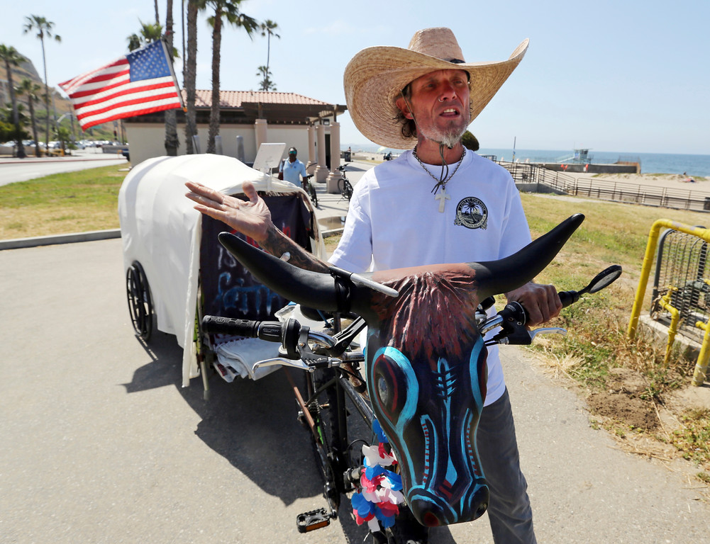 """. David Foute, 53, of Galveston, Texas, makes a stop on his months-long planned trek in honor of U.S. military veterans in a \'covered wagon,\' which he tows on his bicycle, Sunday, May 28, 2017, at Will Rogers State Beach in the Pacific Palisades area of Los Angeles. Foute left Galveston on May 13, enroute to Oregon later this summer. \""""I\'m not a veteran, but I\'m trying to give back what they gave so much for us. I\'m able to do what I\'m doing because of them.\"""" (AP Photo/Reed Saxon)"""