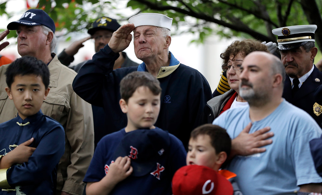 . Bob Skorny, center, who served as a Navy electronic technician third class on the USS Midway, chokes up as people salute during a Memorial Day observance, Monday, May 29, 2017, in Bridgewater, N.J. (AP Photo/Julio Cortez)