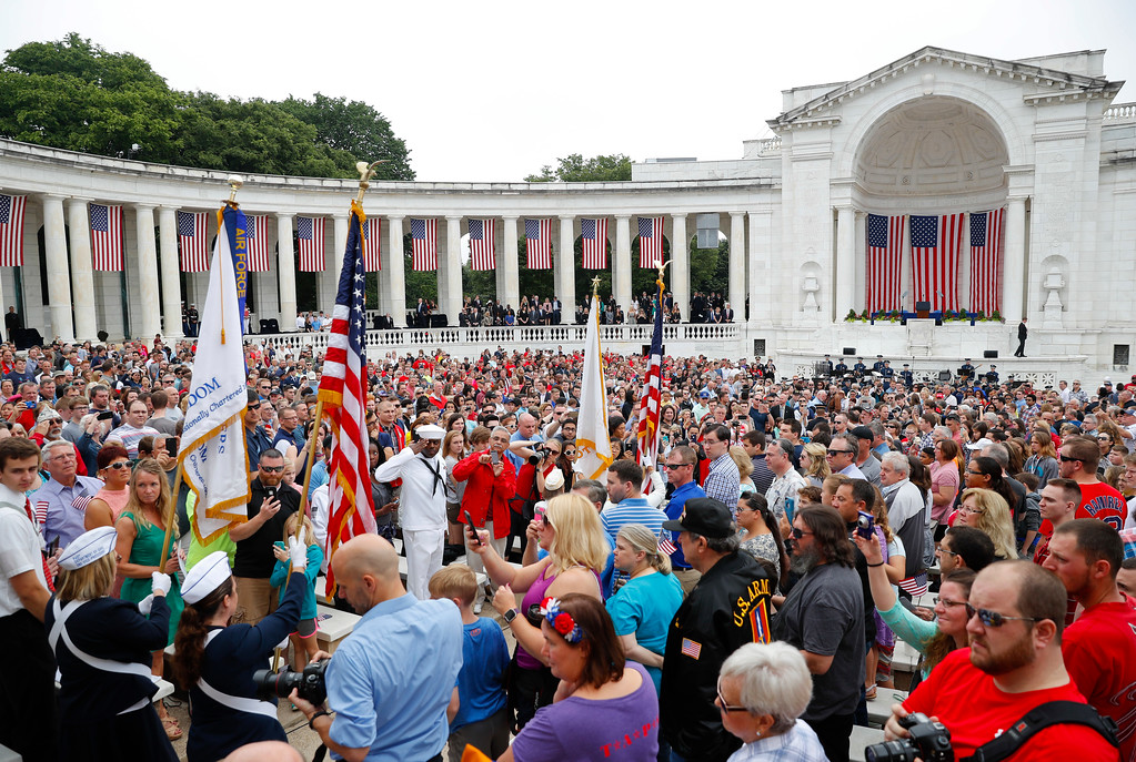 . Members of the audience stand as flag bears walk into the Memorial Amphitheater in Arlington National Cemetery in Arlington, Va., Monday, May 29, 2017, to begin the Memorial Day ceremony. (AP Photo/Pablo Martinez Monsivais)