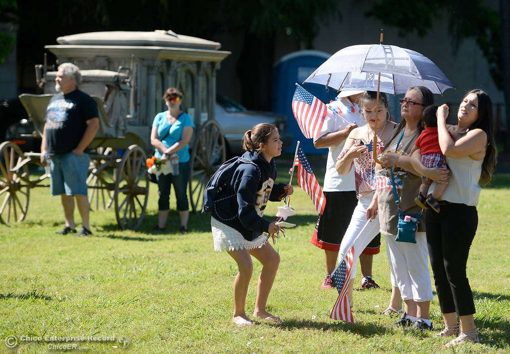 . A family keeps cool beneath an umbrella during the Memorial Day Ceremony held at the Chico Cemetery in Chico, Calif. Monday, May 28, 2018. (Bill Husa -- Enterprise-Record)