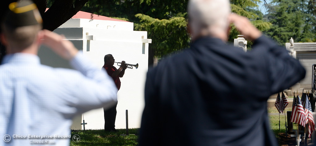 . Veterans salute as Jesse Rosenquist plays Taps during the Memorial Day Ceremony held at the Chico Cemetery in Chico, Calif. Monday, May 28, 2018. (Bill Husa -- Enterprise-Record)
