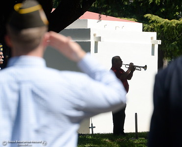 Veterans salute as Jesse Rosenquist plays Taps during the Memorial Day Ceremony held at the Chico Cemetery in Chico, Calif. Monday, May 28, 2018. (Bill Husa -- Enterprise-Record)