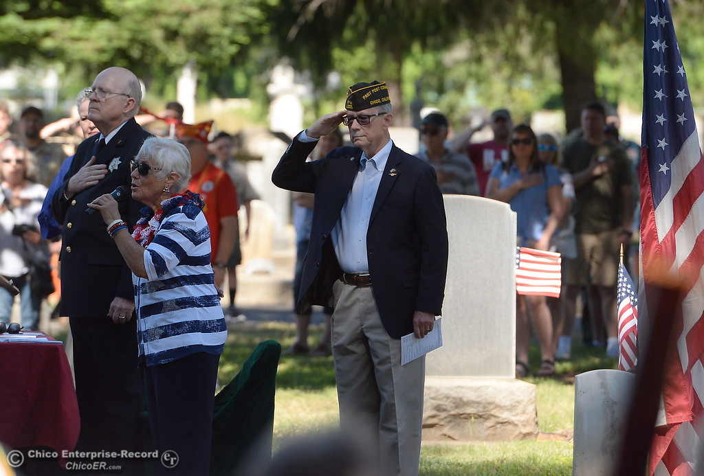 . Master of Ceremonies Larry Wahl salutes at right while Marion Compton sings the Star Spangled Banner during the Memorial Day Ceremony held at the Chico Cemetery in Chico, Calif. Monday, May 28, 2018. (Bill Husa -- Enterprise-Record)