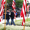 Goshen police retirees Jeff Schrock, left, and Randy Kantner walk the American flag to the Elkhart County War Memorial Monday morning as part of Memorial Day services.
