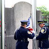 Goshen police retirees Jeff Schrock, left, and Randy Kantner prepare to raise the flag over the Elkhart County War Memorial in downtown Goshen Monday morning as part of Memorial Day services.