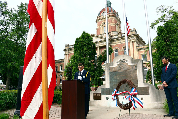 VFW chaplain John Alheim leads the group assembled at the Elkhart County War Memorial in prayer Monday morning during Memorial Day services. To the right is Goshen Mayor Jeremy Stutsman.