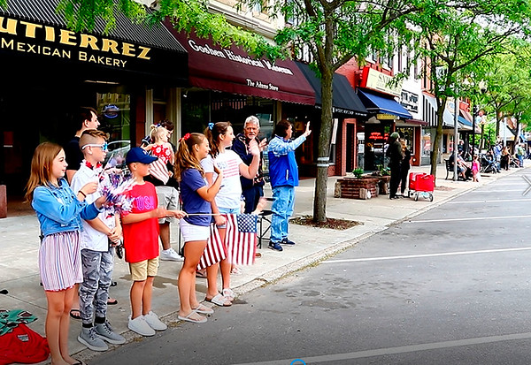 The Maust family waves at passing vehicles during the Goshen Memorial Day parade Monday morning. From left are Maylin, Kahler, Lain Maust, Izzi and Lyla. In back is Isaac Maust.