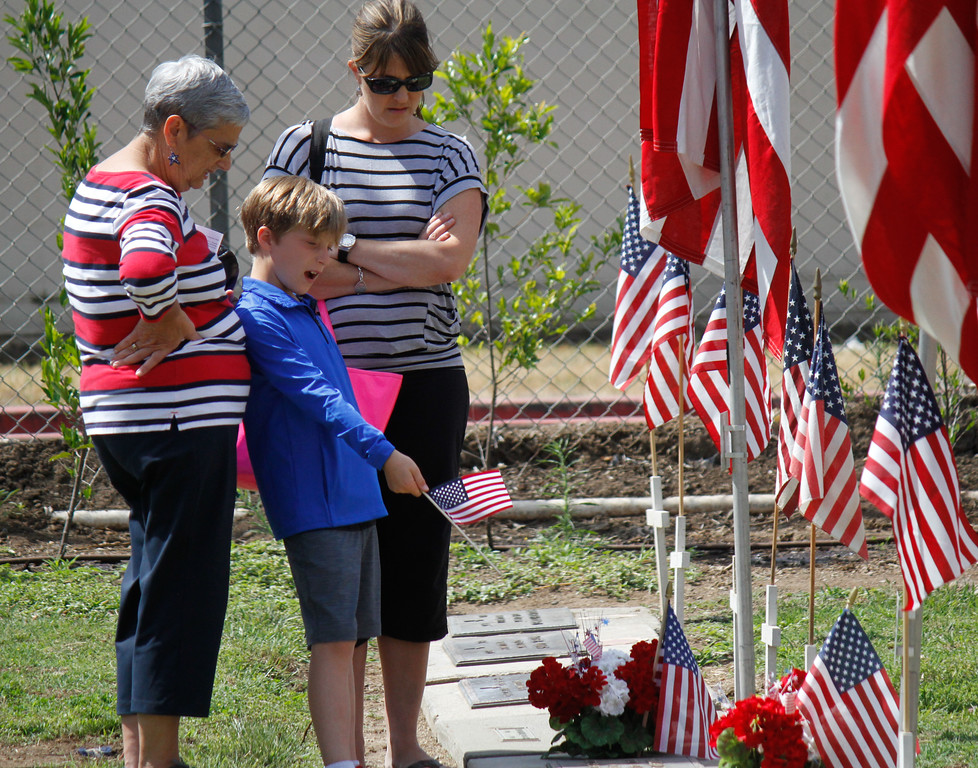 . Susan Vanella, Jack Vanella (8) and Janette Vanella, left to right, visit the Susan\'s husband Harlan Peterson a WWII veteran during the Memorial Day Ceremony Monday May 29, 2017 at the Chico Cemetery in Chico, California. (Emily Bertolino -- Enterprise-Record)