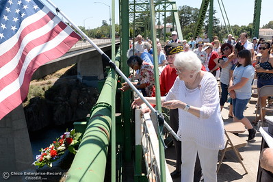 Sherry Morehouse tosses the ceremonial wreath over the rail into the Feather River below during the Memorial Day Ceremony on the Green Bridge in Oroville, Calif. Mon. May 30, 2016. (Bill Husa -- Enterprise-Record)