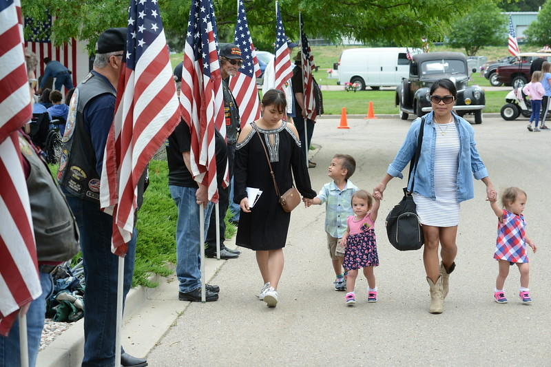 Wengelen Brummett walks with her children past the flag-bearing members of the Patriot Guard Riders during Memorial Day events at Resthaven Memory Gardens north of Loveland on Monday, May 28, 2018. Her children are 20-month-old twins Allie and Aria, 3-year-old Camden and Alexandra Brummett. Wengelen Brummett said the family was visiting from Nevada, where her husband serves in the Navy. Patriot Guard member Cliff Mahrling of Loveland watches the family go past. (Photo by Craig Young / Loveland Reporter-Herald)