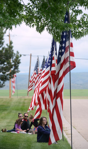 Loveland resident Sandy Streich, right, and the Battige family of Kyle, Kristen, Lilah, 4, and Clara, 2, sit among flags that were raised for Memorial Day events at Resthaven Memory Gardens north of Loveland on Monday, May 28, 2018. (Photo by Craig Young / Loveland Reporter-Herald)