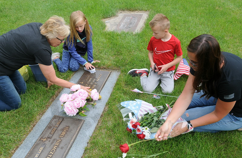 Members of the family of Maggie Carson, left, clean up the headstones of her father and mother after the Memorial Day ceremony at Loveland Burial Park on Monday morning, May 28, 2018. Carson's daughter, Elizabeth Coxon, right, and Coxon's children, Macy, 8, and Declan, 5, helped with the work. (Photo by Craig Young / Loveland Reporter-Herald)