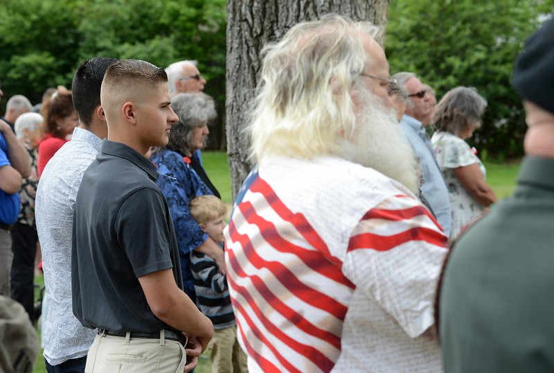 Loveland High School graduates Niko Navas, obscured at far left, and Colby Struckman stand among military veterans, family members and people from the community during the Memorial Day ceremony at Loveland Burial Park on Monday morning, May 28, 2018. Navas is a corporal in the Marine Corps, and Struckman is a member of the Army ROTC at Colorado State University.  (Photo by Craig Young / Loveland Reporter-Herald)