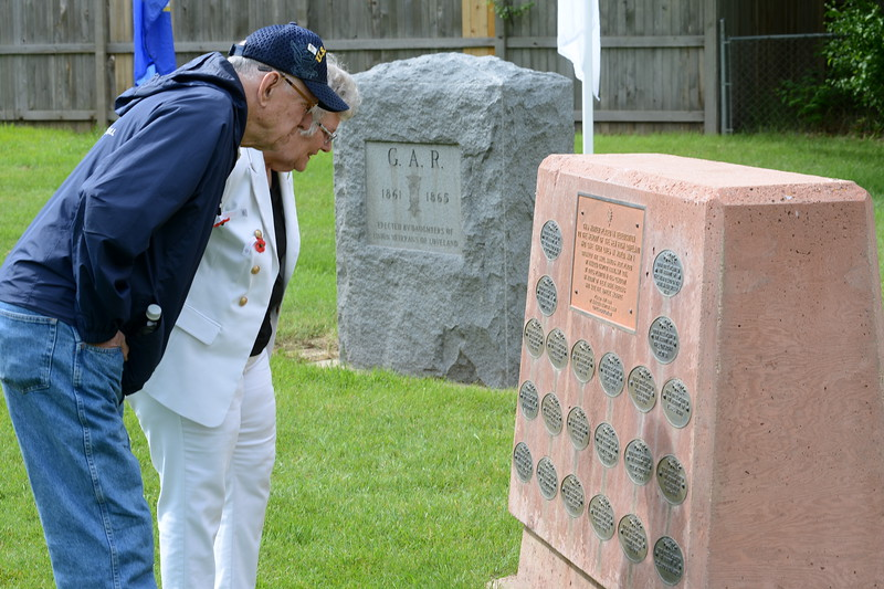 Robert and Silvia Fiscus look at the metal plaques that once were placed at the bases of trees planted in memory of local veterans in Loveland Burial Park. Robert, a Navy veteran of the Korean War, and Sylvia, a member of the Air Force from 1963 to '65, attended the Memorial Day ceremony at Loveland Burial Park on Monday morning, May 28, 2018. (Photo by Craig Young / Loveland Reporter-Herald)